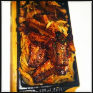 spicy marinated pork belly over kimchi